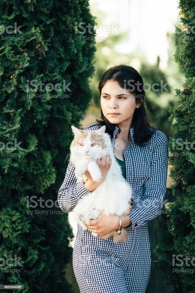 Cute girl holds spotted cat in her arms zbiór zdjęć royalty-free