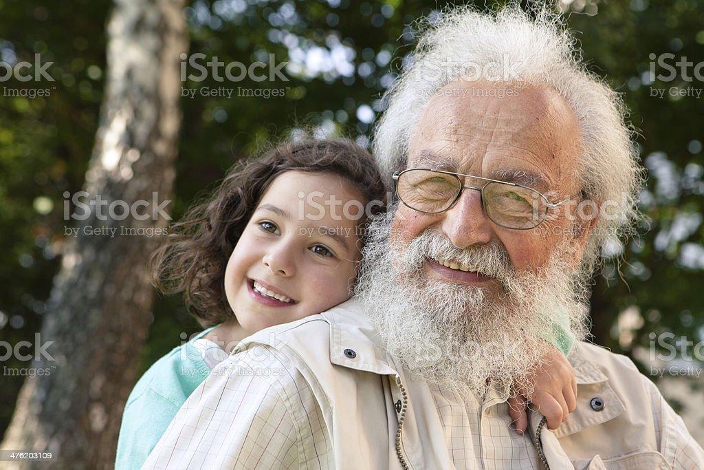 cute girl hugging bearded grandfather royalty-free stock photo