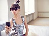 Cute girl in adult dress taking selfie