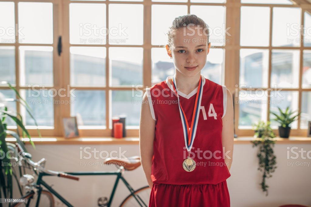 Cute young girl in basketball jersey with a gold medal in living room
