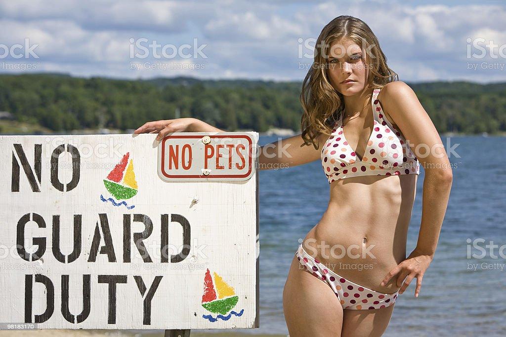 Cute girl in bikini next to sign royalty-free stock photo
