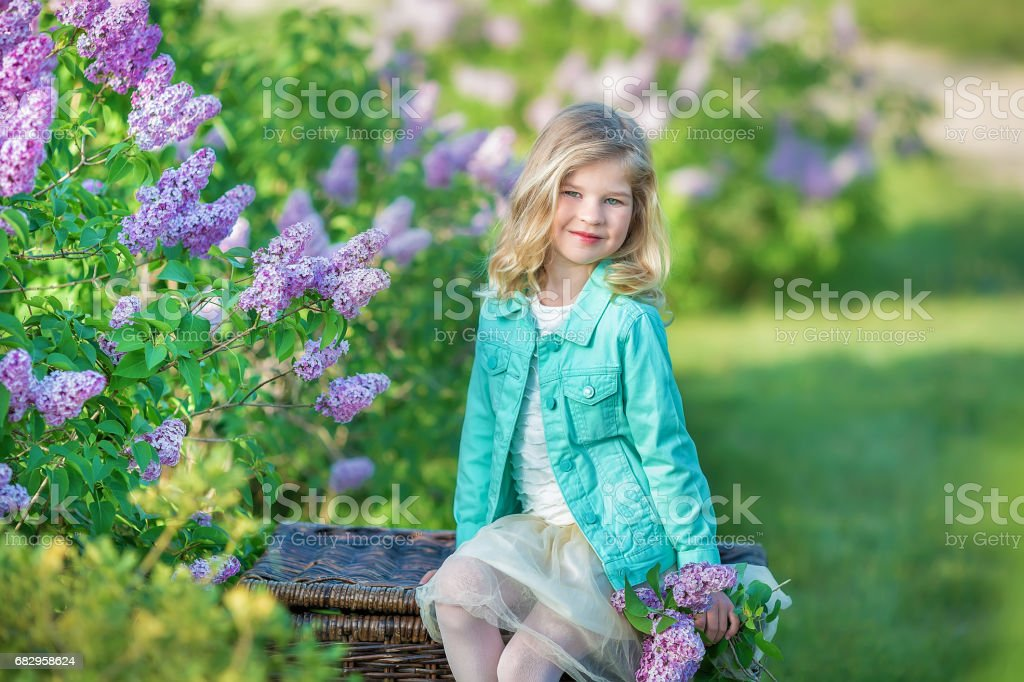 Cute girl in blue jackets with fairy airy skirt standing close to lilac bush royalty-free stock photo