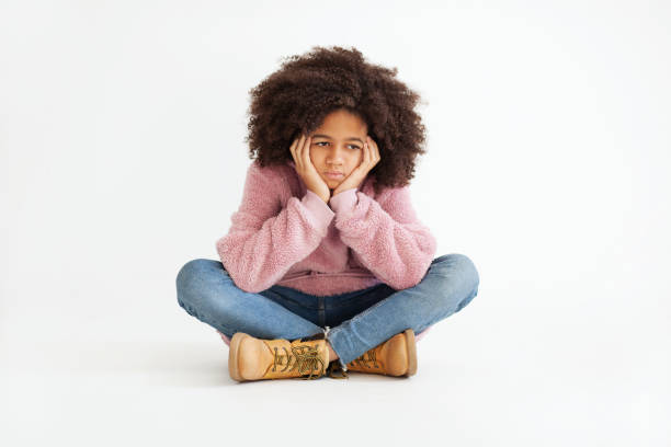 Cute girl in casual clothing is feeling sad Cute girl in casual clothing is feeling sad. Portrait against white background cross legged stock pictures, royalty-free photos & images