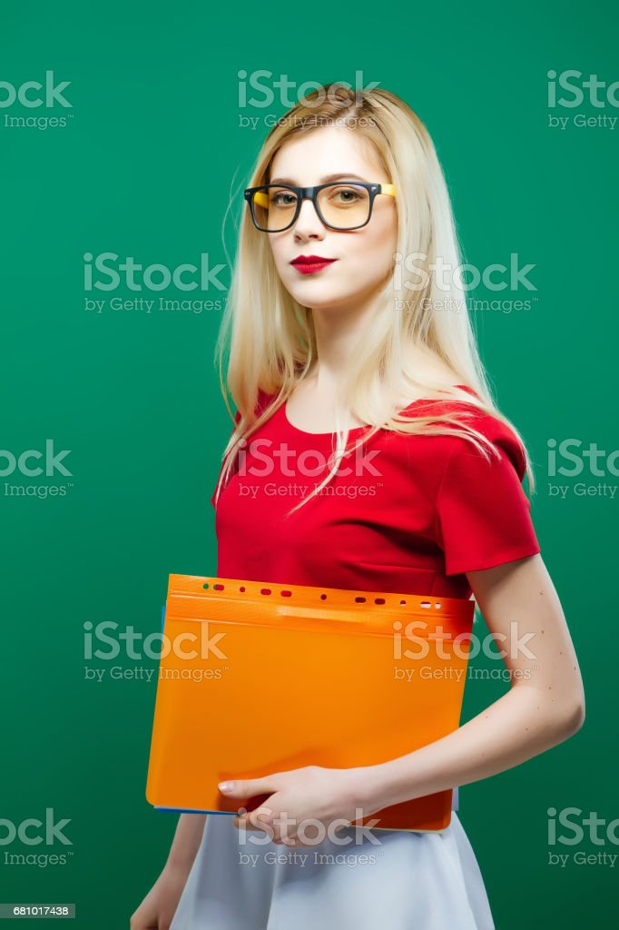 Cute Girl in Eyeglasses with Folder of Documents in Hands is Standing on Green Background in Studio. Education Concept. royalty-free stock photo