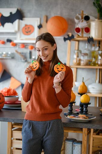 Cute smiling girl, standing in kitchen and posing with Halloween cookies.