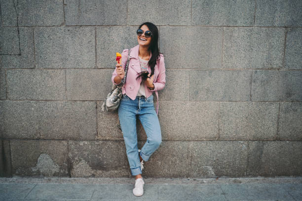 Cute girl in the city eating ice-cream Teenage girl enjoying an ice-cream leather jacket stock pictures, royalty-free photos & images
