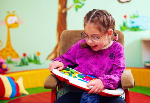 cute girl in wheelchair playing with developing toy in kindergarten for children with special needs stock photo