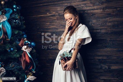 istock Cute girl in white dress holding gift box 590079878