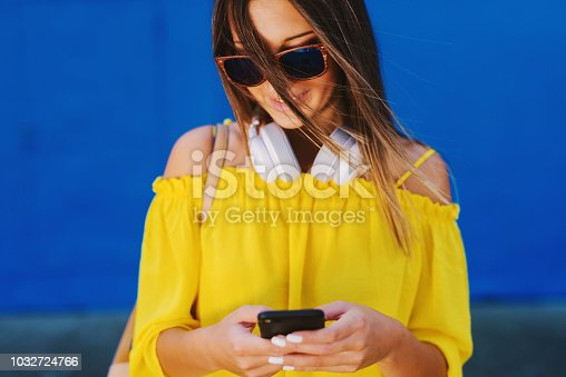 istock Cute girl in yellow shirt standing in front of blue wall and holding cell phone with smile on her face. 1032724766