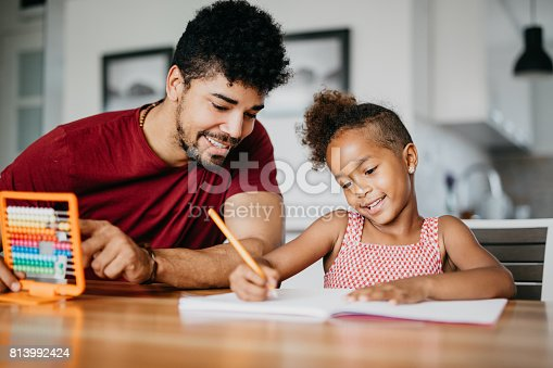 istock Cute girl is doing math with a help of her dad 813992424