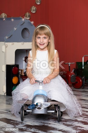 486524205 istock photo Cute girl is playing with toy cars. Rides a toy typewriter airplane. Happy childhood. 1185283645