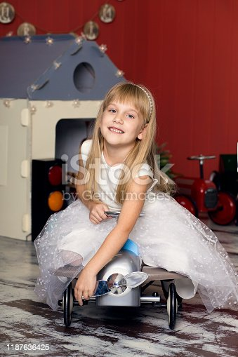 486524205 istock photo Cute girl is playing with toy cars. Rides a toy typewriter airplane. Happy childhood 1187636425
