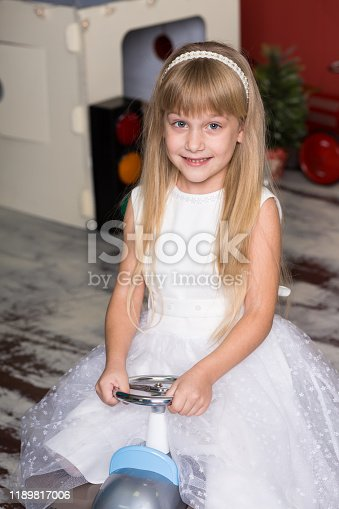 486524205 istock photo Cute girl is playing with toy cars. Rides a toy typewriter airplane. Happy childhood. 1189817006
