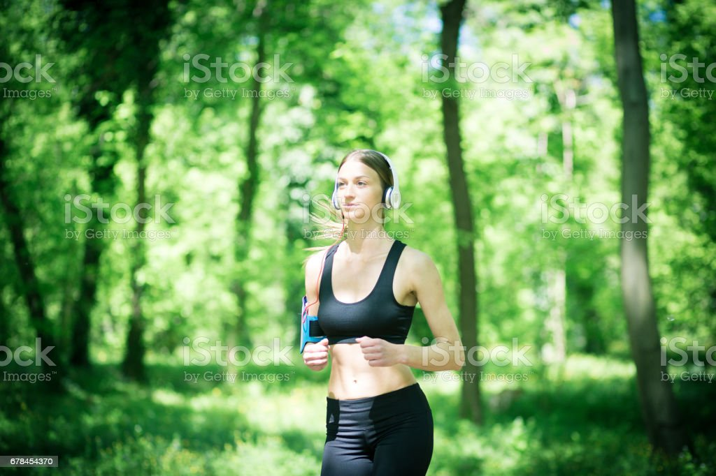 Cute girl, jogging in the park, wearing headphones, listening music royalty-free stock photo