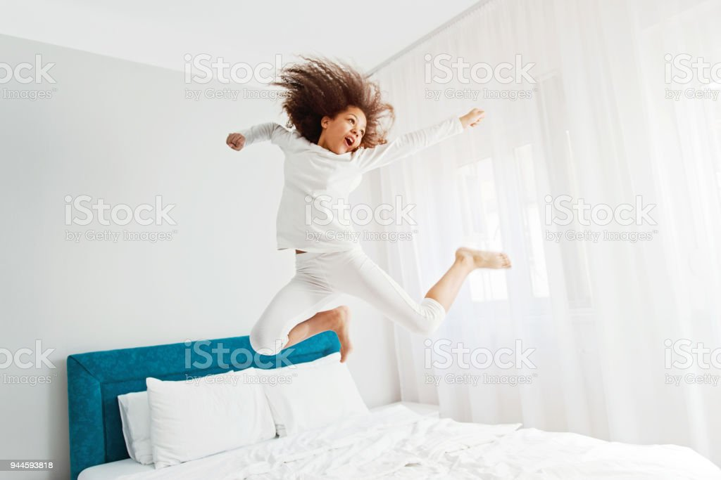 Cute girl jumping on the bed, happiness, joyful stock photo