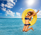 Portrait of cute girl in bikini and sunglasses jumps for joy with big yellow swimming ring against the sea