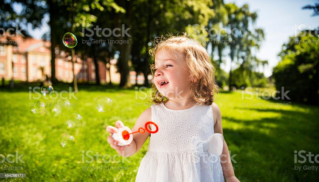 Cute Girl laughing at flying bubbles royalty-free stock photo