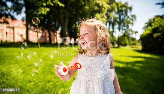 istock Cute Girl laughing at flying bubbles 454266177