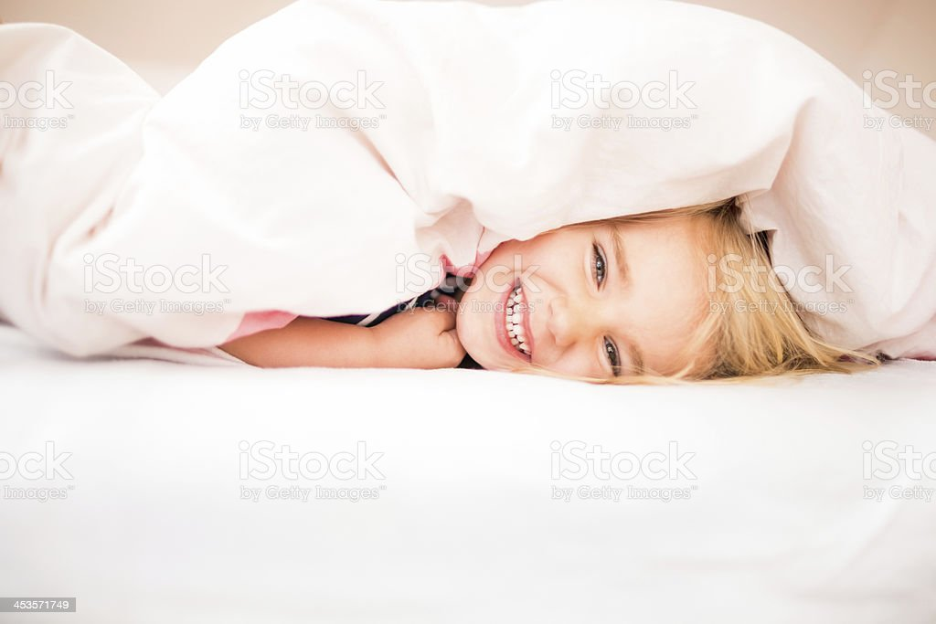 Cute girl laughing in bed royalty-free stock photo
