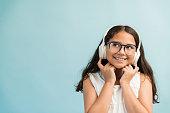 Thoughtful female child looking up while enjoying music against plain background