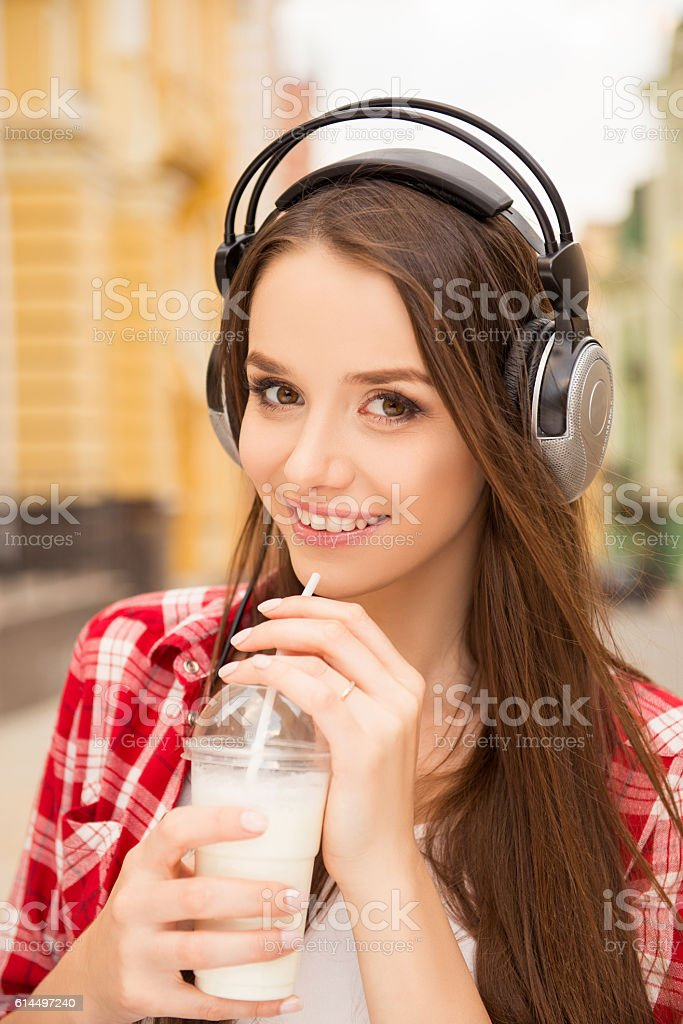 Cute Girl Listening To Music On Headphones Drinking A