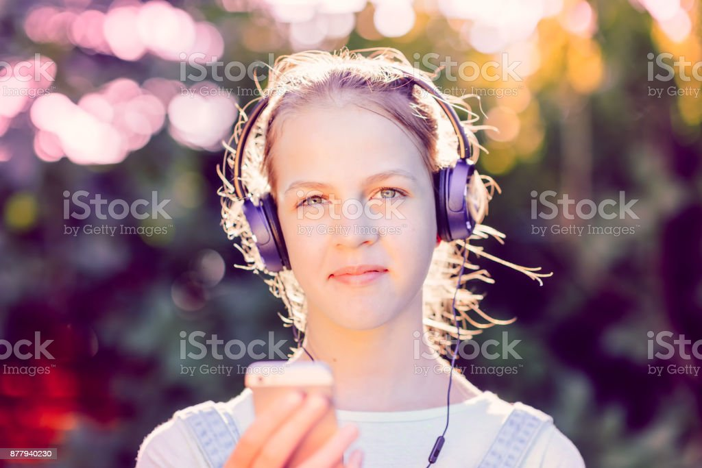 Cute girl listening to music with headphones outdoor - looking at camera stock photo