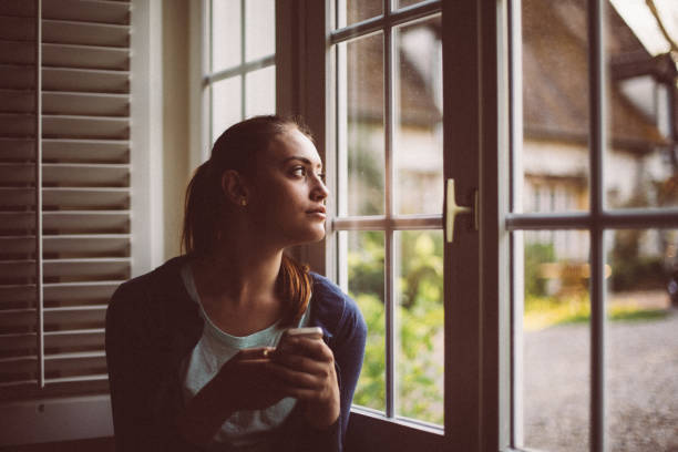 Cute girl looking through the window Woman at home texting on cell phone central europe stock pictures, royalty-free photos & images