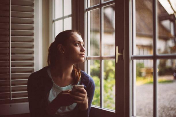 fille mignonne regardant par la fenêtre - europe centrale photos et images de collection