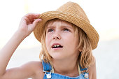 Portrait of charming Caucasian little girl wearing dungaree and straw hat looking up attentively with open mouth on blurred background