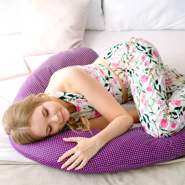 Cute girl lying in bed with body pillow. Concept of comfortable sleep. stock photo