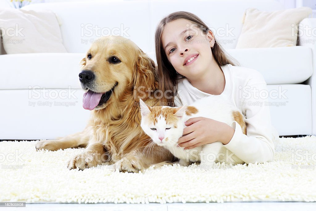 Cute girl lying on the white carpet with pets. royalty-free stock photo