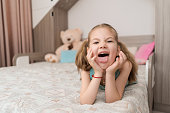 Lovely carefree kid portrait making sweet, funny faces while lying on her bed in her room