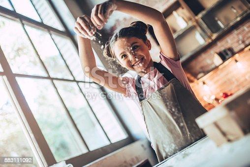 istock Cute girl on kitchen. 883111092