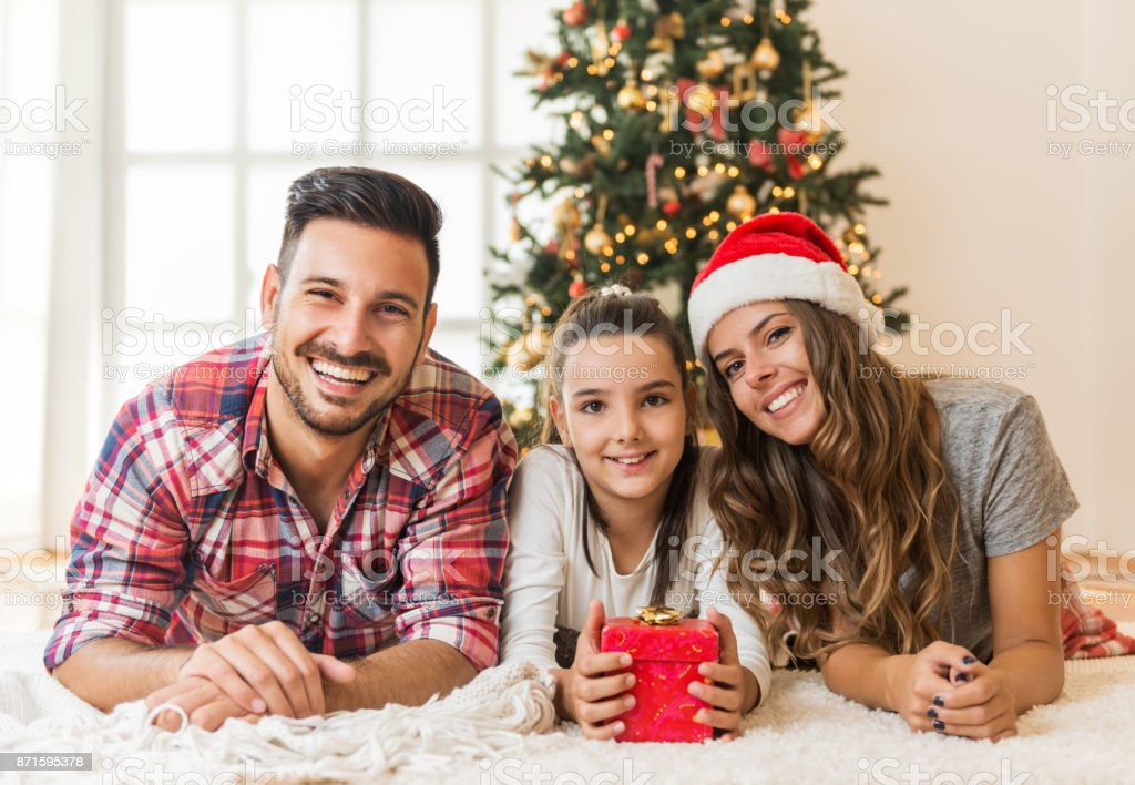 Cute girl opening a magical present on a Christmas morning with her family stock photo
