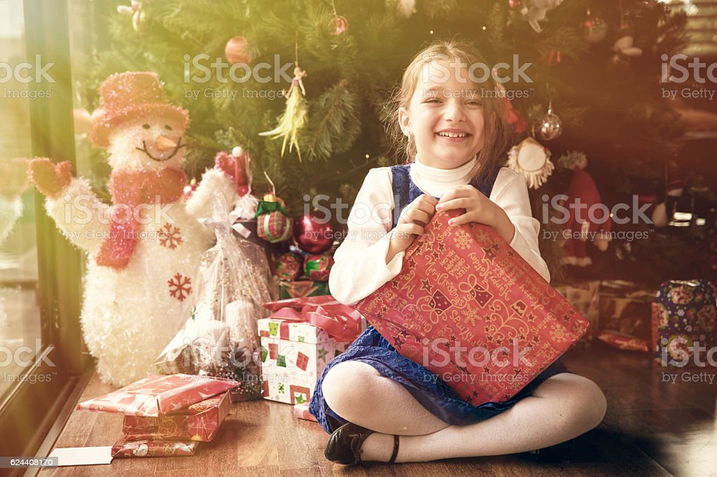 Cute girl opening her Christmas gifts stock photo