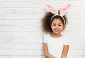 Cute girl over a brick wall with bunny ears