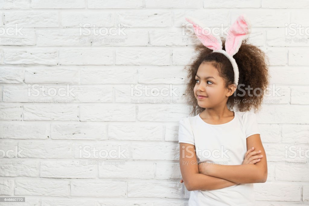 Cute girl over a brick wall with bunny ears stock photo
