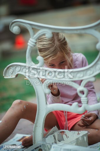 A Cute 6-7-year-old Blonde hair Girl painting renovating an old bench outdoors with white paint and a paintbrush.  She is concentrating and doing a precise and good job.  She has a ponytail and is concentrating on the skill and job.