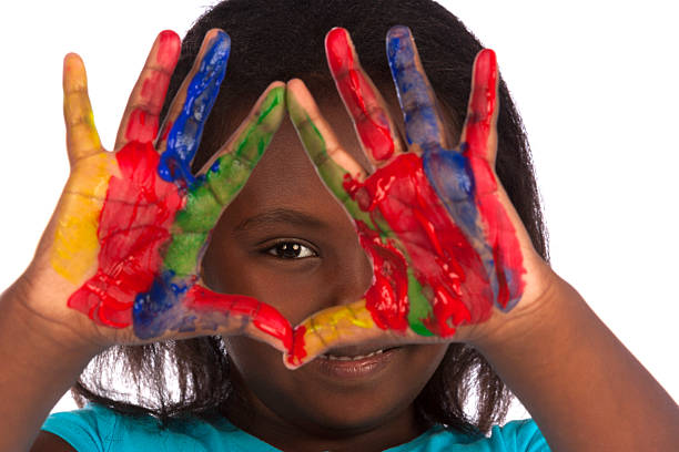 Cute girl peeks through painted hands stock photo