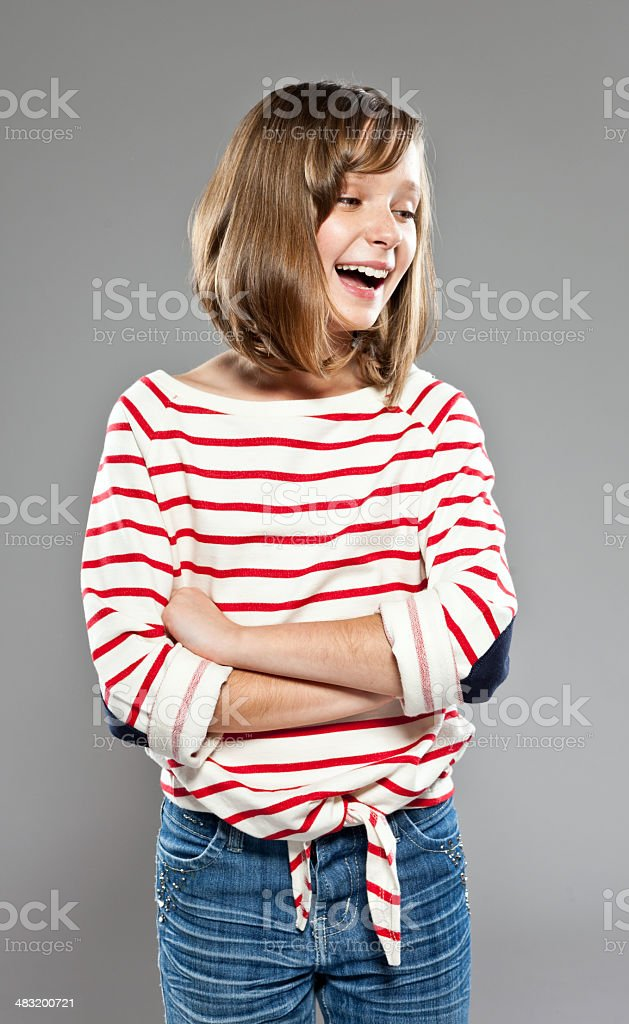 Cute girl Portrait of cute girl wearing striped blouse and jeans, standing against grey background with arms crossed and laughing, Studio shot. 10-11 Years Stock Photo