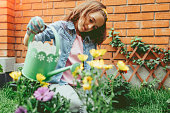 Cute girl planting flowers in backyard. She is sitting in the grass and watering plant with water can.