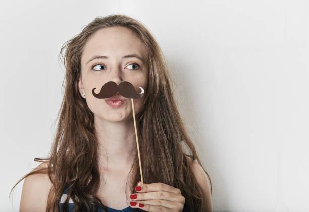 niedliche mädchen versucht spielerisch auf gefälschte schnurrbart - schnurrbart themenpartys stock-fotos und bilder