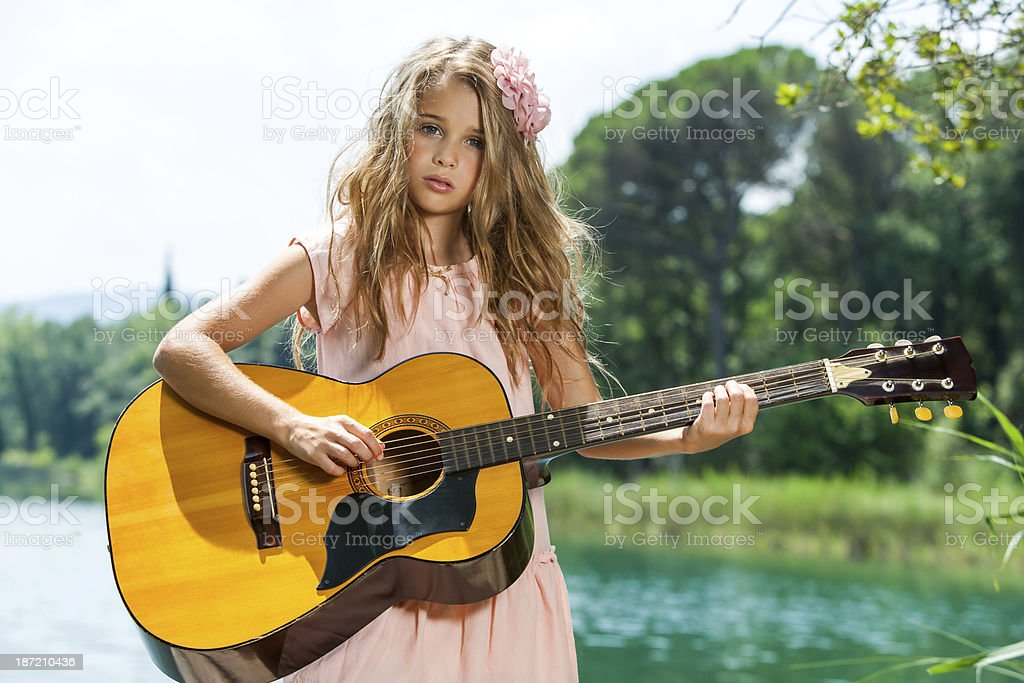 Cute girl playing guitar at lake. royalty-free stock photo