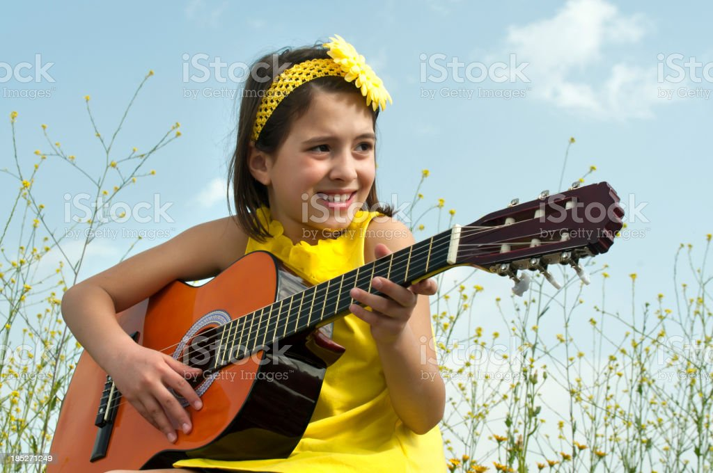 Cute girl playing guitar to daisy field royalty-free stock photo