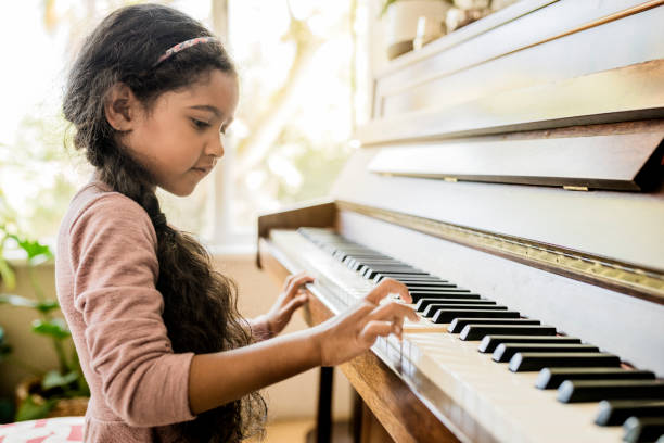 Cute girl playing piano at home Side view of girl playing piano. Cute female child is practicing on musical instrument. She is at home. pianist stock pictures, royalty-free photos & images