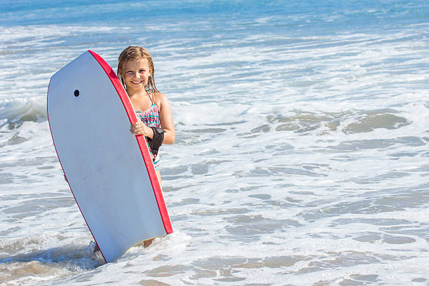 Cute girl playing with a boogie board in the ocean stock photo