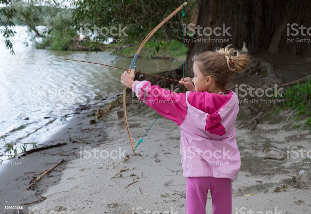 Cute girl playing with bow and arow outside at the riverbank stock photo