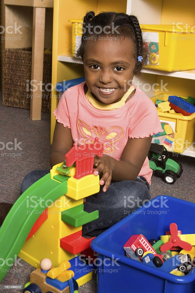 Cute girl playing with toy cars in classroom royalty-free stock photo
