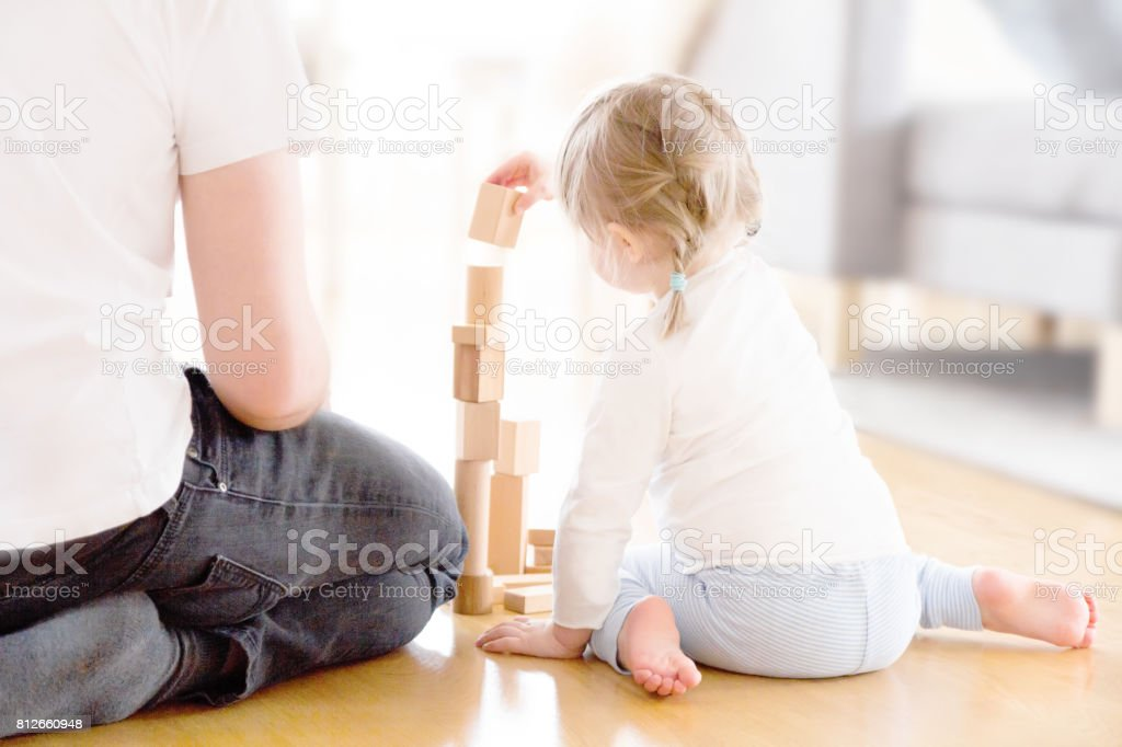 Cute girl playing with wooden blocks ont he floor with her father stock photo