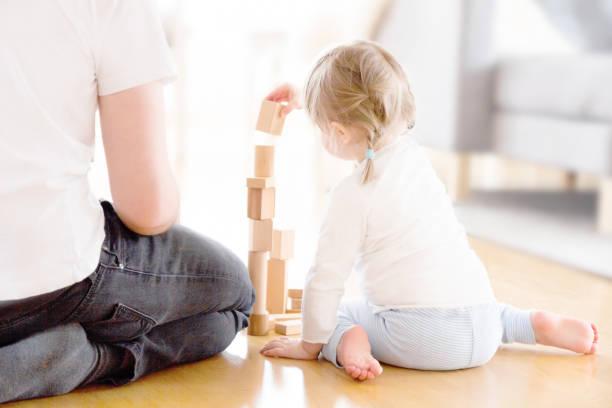 Söt flicka som leker med träklossar på golvet med hennes far bildbanksfoto